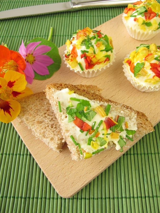 Pralines de beurre persillé avec les fleurs comestibles sur le pain photographie stock libre de droits