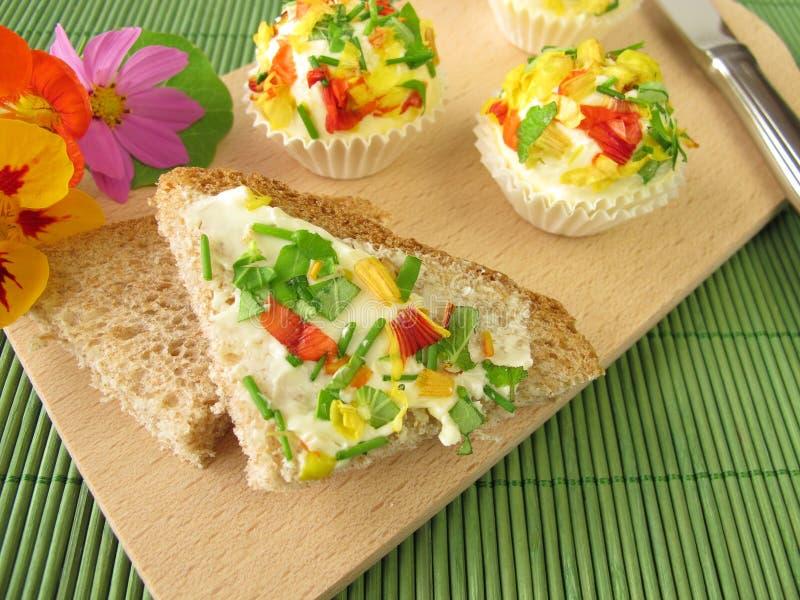 Pralines de beurre persillé avec les fleurs comestibles sur le pain photos libres de droits