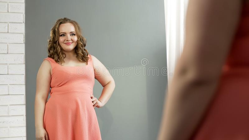 Pralle Dame, die im Spiegel mit reizend Lächeln, Selbstvertrauen, Körperpositiv schaut stockfoto