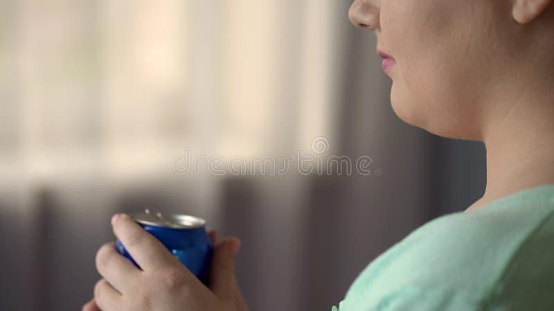Pralles weibliches trinkendes Soda oder Bier an der Partei allein, ungesunde Fertigkost verursacht Übergewicht stockfotos