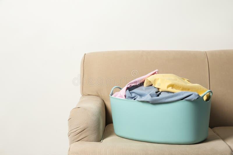 Pralniany kosz z brudnym odziewa na kanapie przeciw lekkiemu tłu obraz stock
