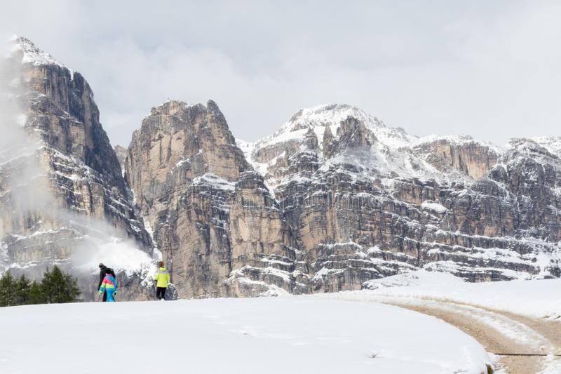 people stroll in alpine scenery with snow-covered meadows along a road royalty free stock images