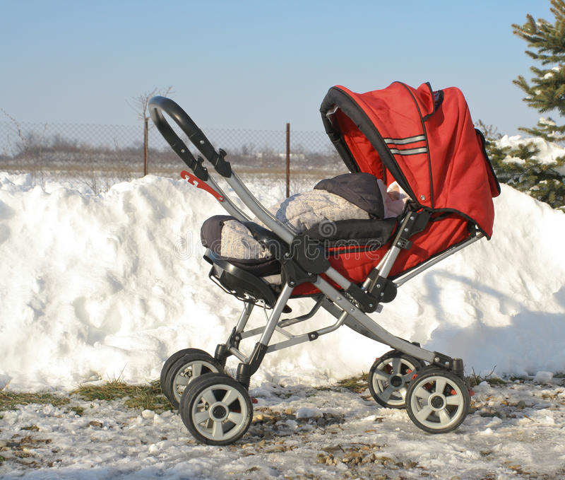 Pram перевозки младенца в зиме стоковые фото