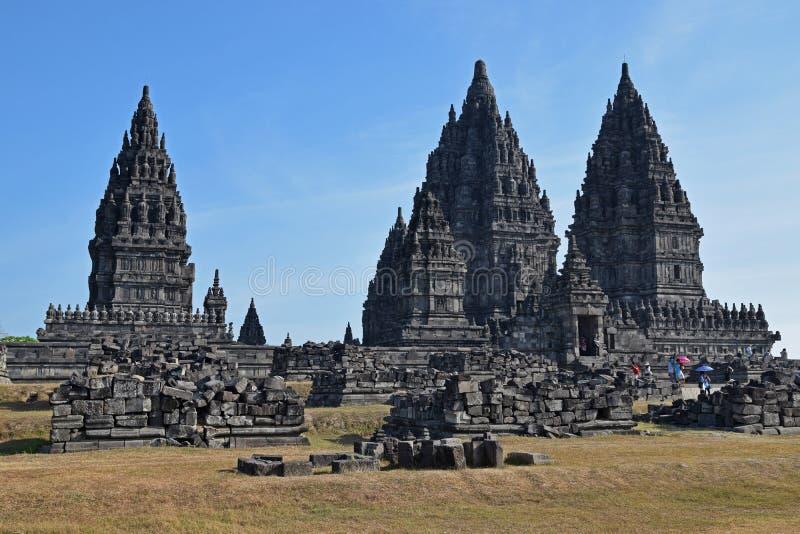 Prambanantempels met steenruïnes en toeristen die paraplu dragen die & het complex verlaten ingaan stock foto
