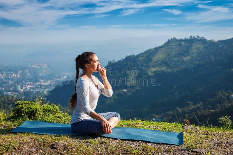 Pranayama das práticas da mulher na pose dos lótus fora fotografia de stock royalty free