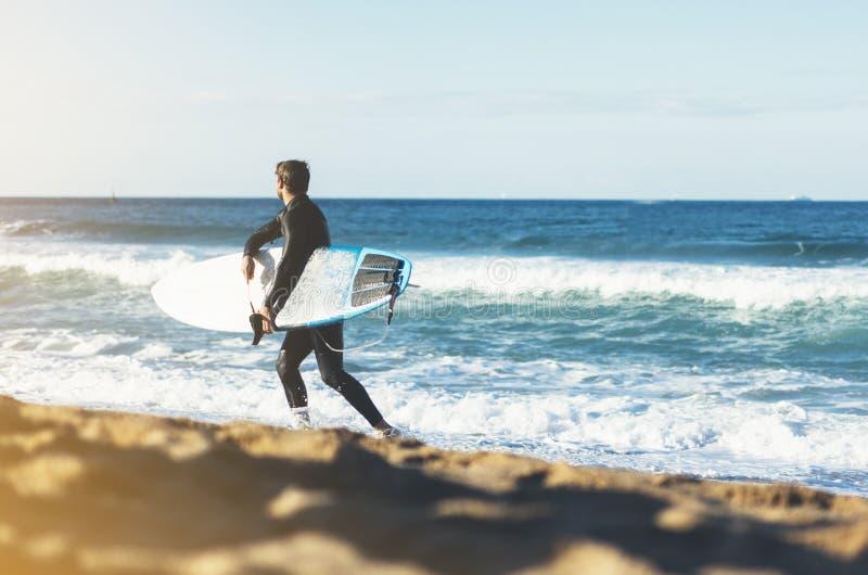 Prancha da terra arrendada do homem do surfista no scape do mar do fundo, litoral da praia da areia Oceano da opinião de perspect foto de stock royalty free