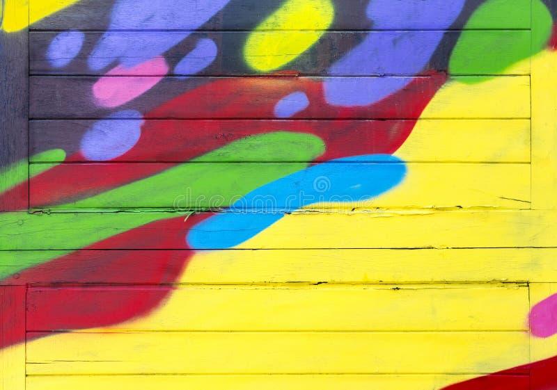 A prancha de madeira velha pintada em vermelho, em amarelo, em azul, em brilhante, e é um fundo bonito da textura fotografia de stock