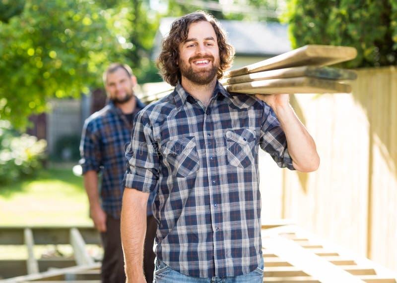 Pranchas de With Coworker Carrying do carpinteiro fora imagem de stock