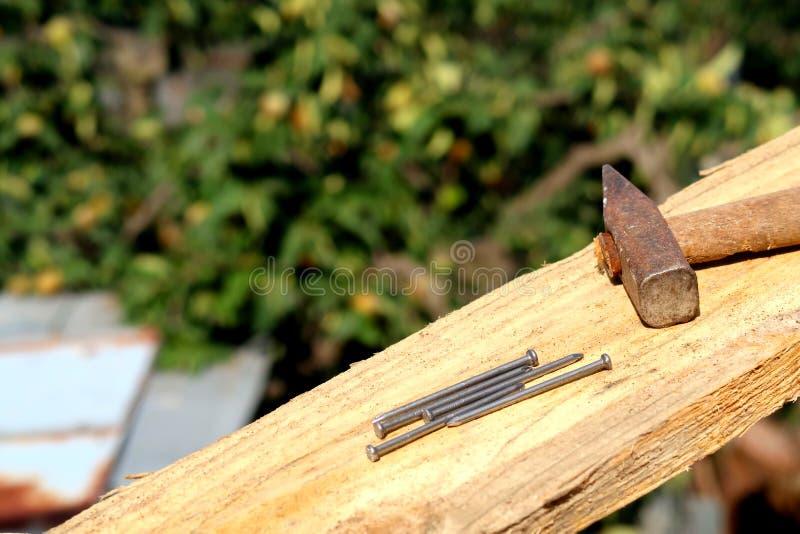 Pranchas de madeira com pregos e martelo no foco em um canteiro de obras imagens de stock royalty free