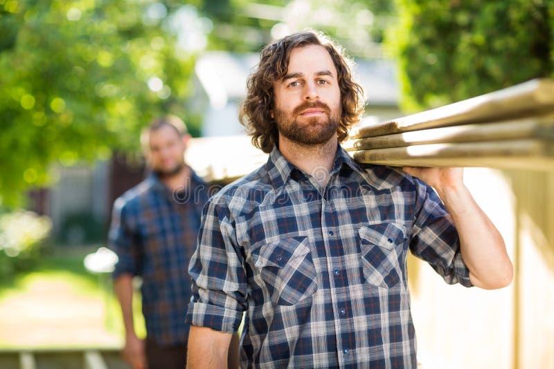 Pranchas de madeira de With Coworker Carrying do carpinteiro imagem de stock
