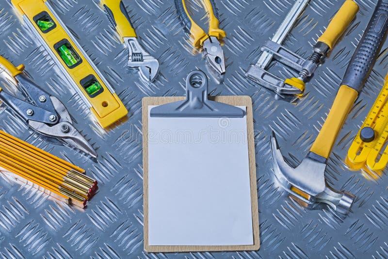 Prancheta brilhante do conceito da construção da versão com papel vazio branco e muitas ferramentas em folha ondulada imagem de stock