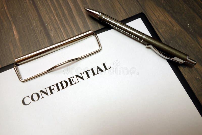 Prancheta com documento confidencial e pena na mesa imagem de stock royalty free