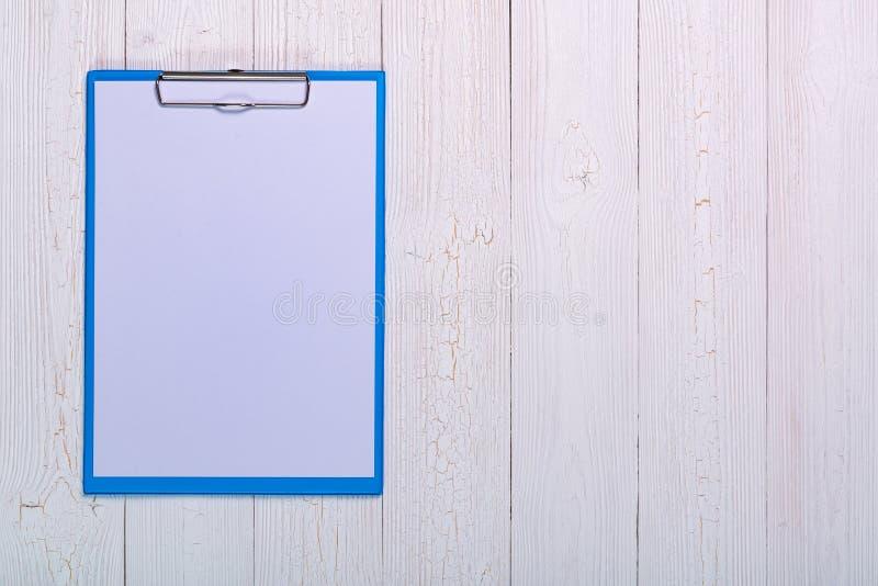 prancheta com a folha vazia do Livro Branco nos wi de madeira da opinião de tampo da mesa fotos de stock royalty free