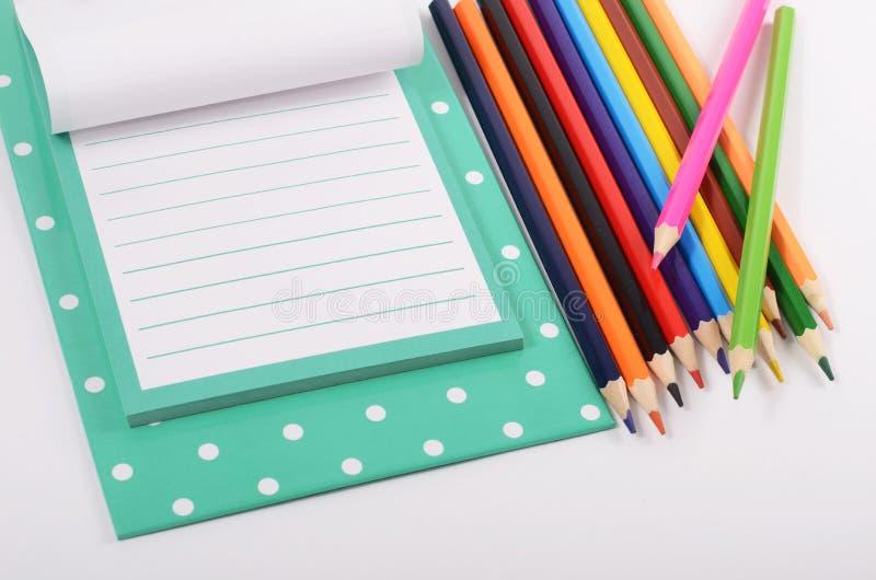 Prancheta com folhas e os lápis coloridos imagens de stock royalty free
