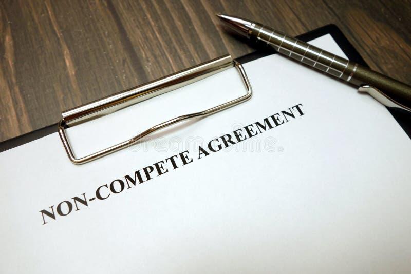 A prancheta com não-compete acordo e pena na mesa fotografia de stock royalty free