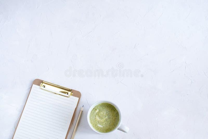 Prancheta com papel vazio ao lado do copo do latte do matcha imagens de stock
