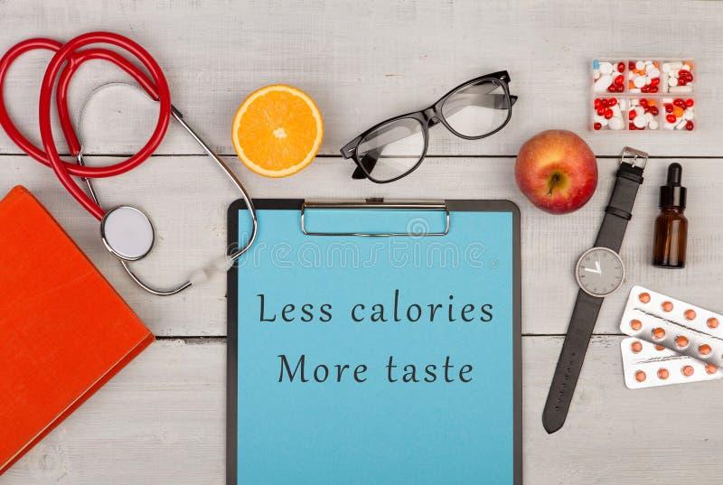 prancheta com texto & x22; Menos calorias mais taste& x22; , livro, comprimidos, monóculos, relógio, fruto e stethoscop imagens de stock royalty free