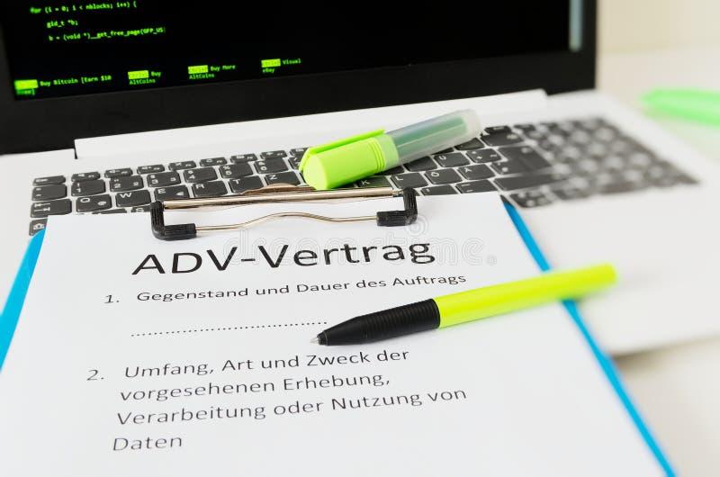 A prancheta com um contrato e a inscrição em ADV-Vertrag alemães em ADV ingleses contratam e assunto e duração do engodo imagens de stock