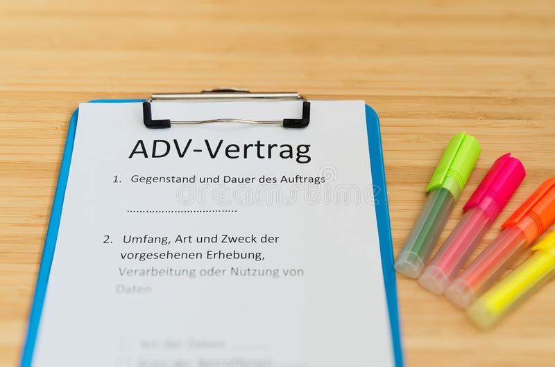 A prancheta com um contrato e a inscrição em ADV-Vertrag alemães em ADV ingleses contratam e assunto e duração do engodo imagem de stock royalty free