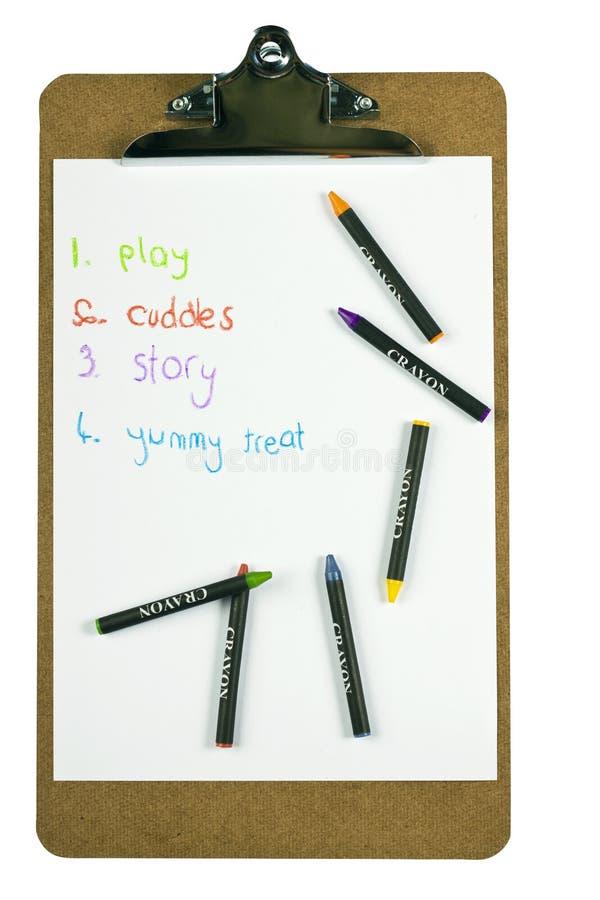 Prancheta com uma lista e os pastéis de tumulto dos childs fotografia de stock royalty free
