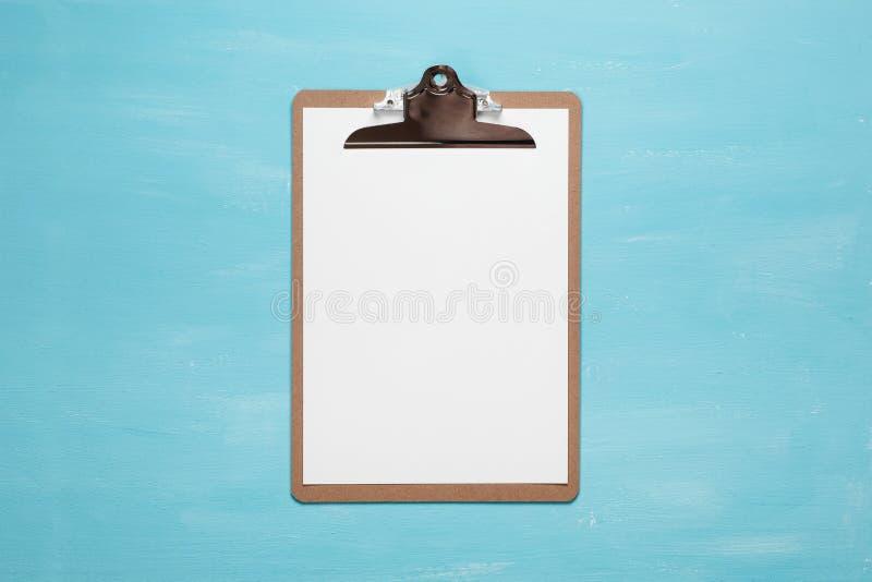 Prancheta vazia no fundo azul pastel da cor com espaço da cópia, estilo mínimo, configuração lisa imagem de stock