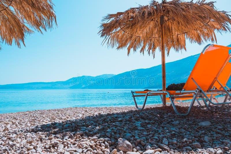 Prange sunbed на Pebble Beach под зонтиком соломы на теплом свете захода солнца стоковые фото
