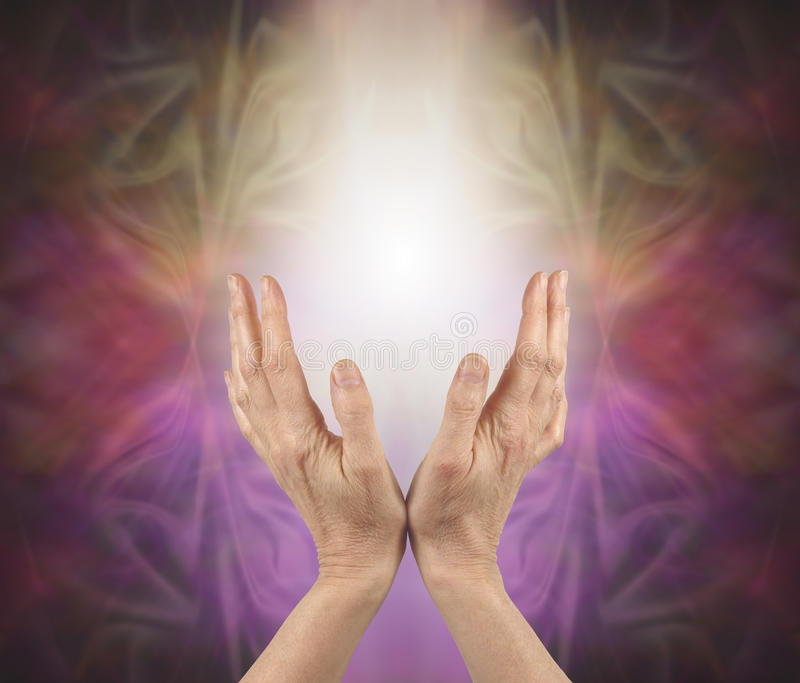 Pranic healer sensing energy. Female hands reaching up into a soft white light with a gold pink and purple energy formation behind and copy space royalty free stock image