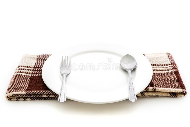 Pranzare la regolazione di posto. Un piatto bianco con la forchetta ed il cucchiaio d'argento immagini stock