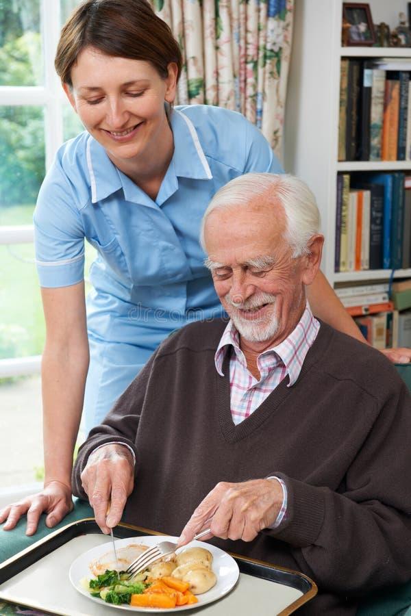 Pranzo del servizio di personale sanitario all'uomo senior fotografia stock libera da diritti