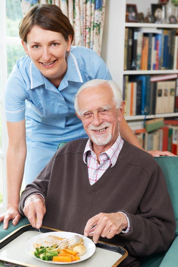 Pranzo del servizio di personale sanitario all'uomo senior immagine stock