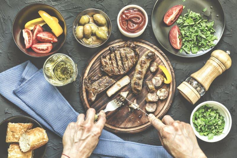 Pranzo della parte A la carte pranzo Ortaggi freschi, una bistecca del barbecue e vari spuntini L'uomo mangia una bistecca succos fotografia stock libera da diritti