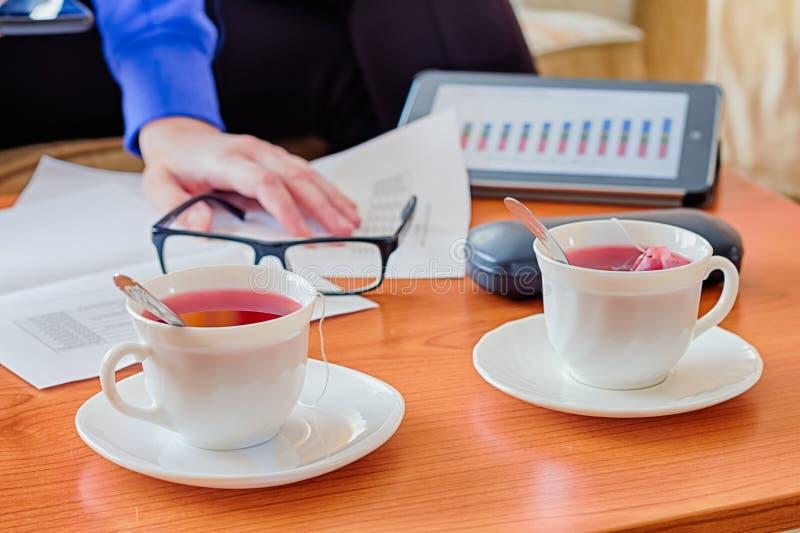 Pranzo di lavoro sulla tavola e sulla tazza di legno di tè immagini stock libere da diritti