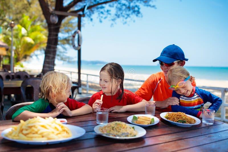 Pranzo di vacanza di famiglia Bambini nel ristorante della spiaggia immagine stock libera da diritti