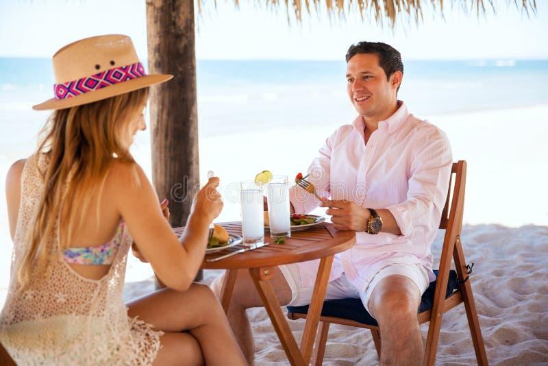 Pranzo mangiatore di uomini con la sua data alla spiaggia immagine stock