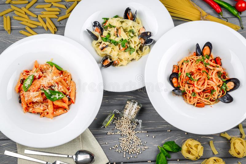 Pranzo Mediterraneo di stile Spaghetti con le cozze e la salsa al pomodoro inscatolate Su una tavola di legno, vista superiore immagini stock