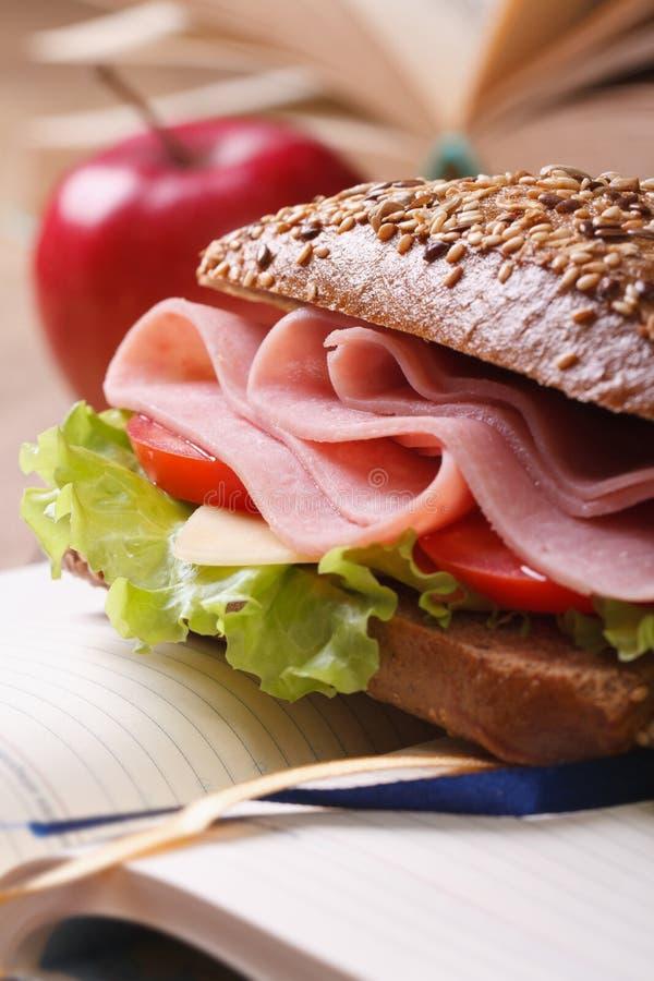 Pranzo: panino con il prosciutto e la mela rossa sul taccuino immagine stock