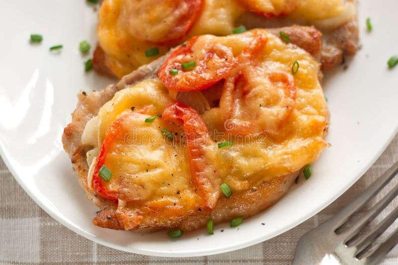 Porco con la cipolla, i pomodori ciliegia ed il formaggio immagine stock