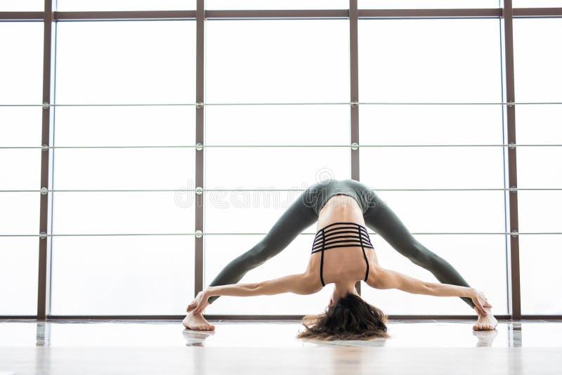 Prasarita Podattanasana. Beautiful yoga woman practice near window yoga room studio background. Yoga concept. stock photos