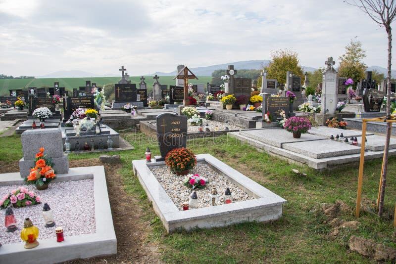 PRASICE,斯洛伐克- 29 10 2015年:坟墓、墓碑和耶稣受难象在传统公墓在小村庄 奉献的蜡烛灯笼 库存图片