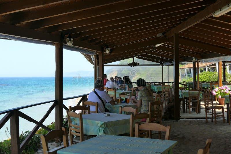 Prasoudi, Corfú, Grecia, junio de 2019 turistas comer el almuerzo en una taberna griega típica con la opinión del mar fotos de archivo libres de regalías