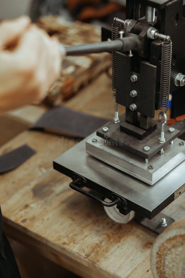 Prasowa maszyna w warsztacie dla robić embossed listom na rzemiennym produkcie który ogrzewa truizm i i logo obraz stock