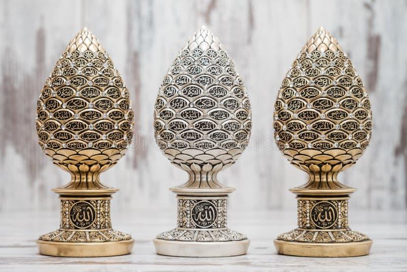 Prata e estatuetas religiosas douradas com os nomes de Allah imagem de stock
