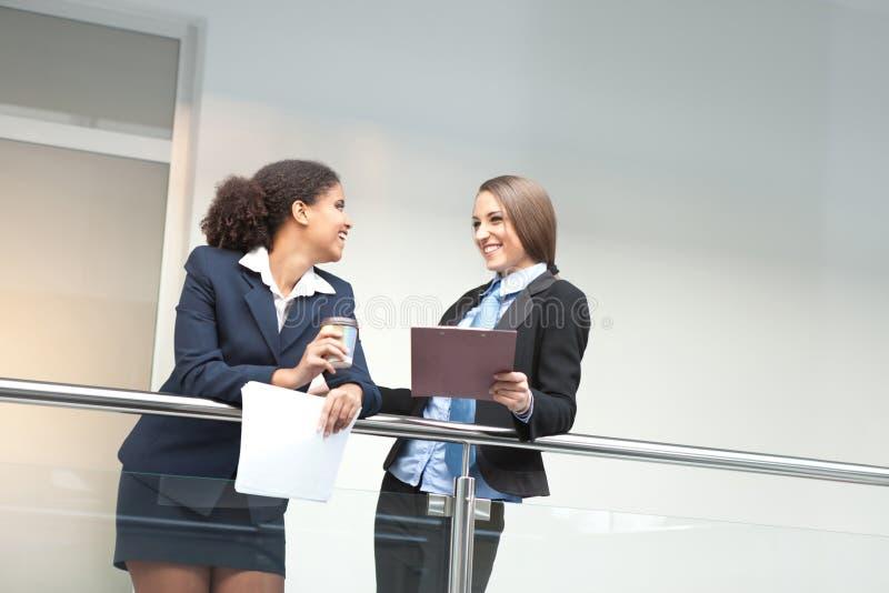 Prata för två le ungt affärskvinnor royaltyfri foto