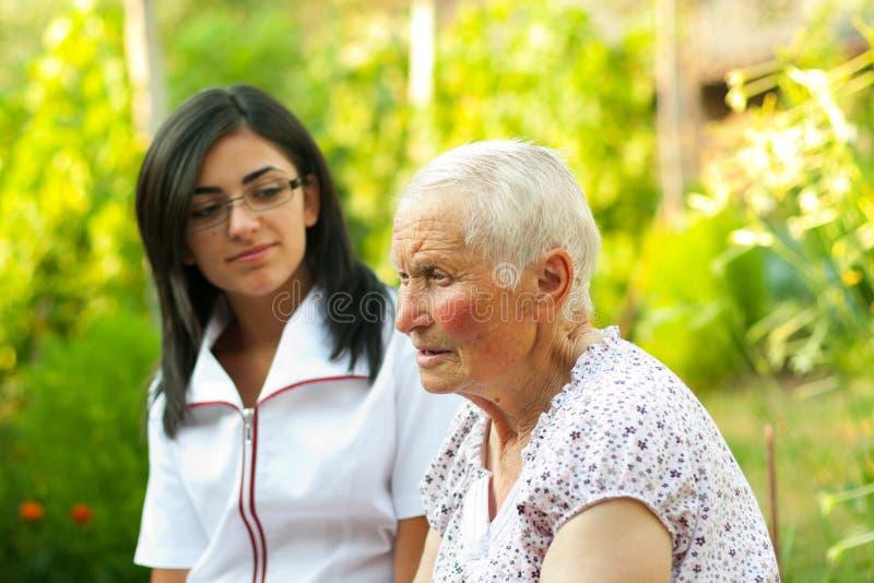 Prata med den sjuka gammalare kvinnan arkivbild