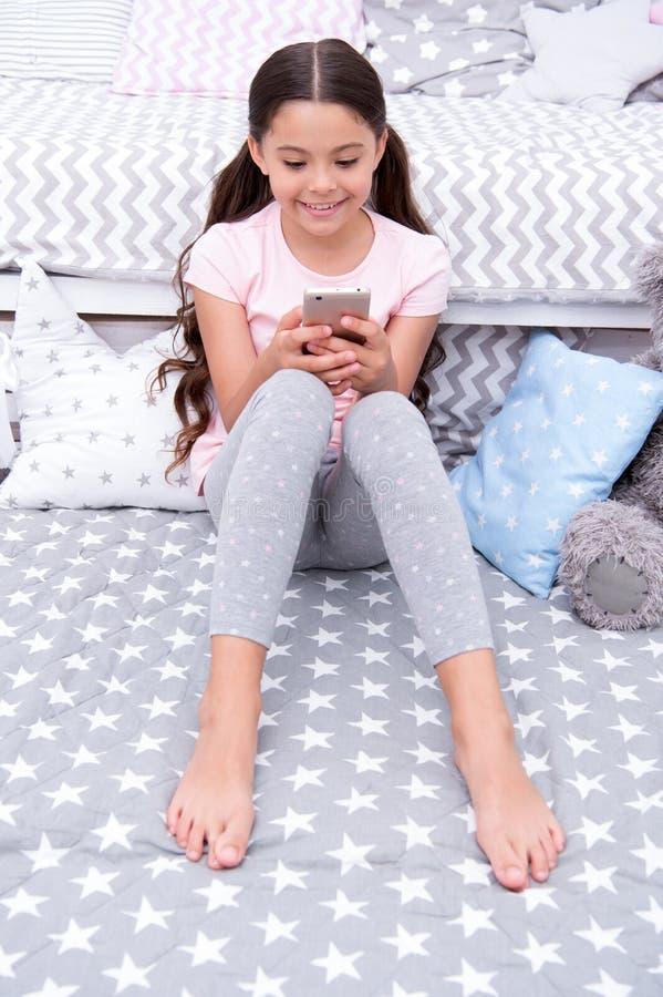 Prata med vännen Flickabarnet sitter på säng med smartphonen i sovrum Ungen förbereder sig att gå att bädda ned Långt hår för fli royaltyfri foto