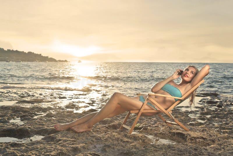Prata på telefonen på stranden royaltyfri bild