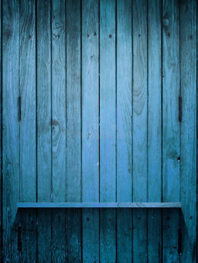 Prateleira azul de madeira na parede com luz fotografia de stock
