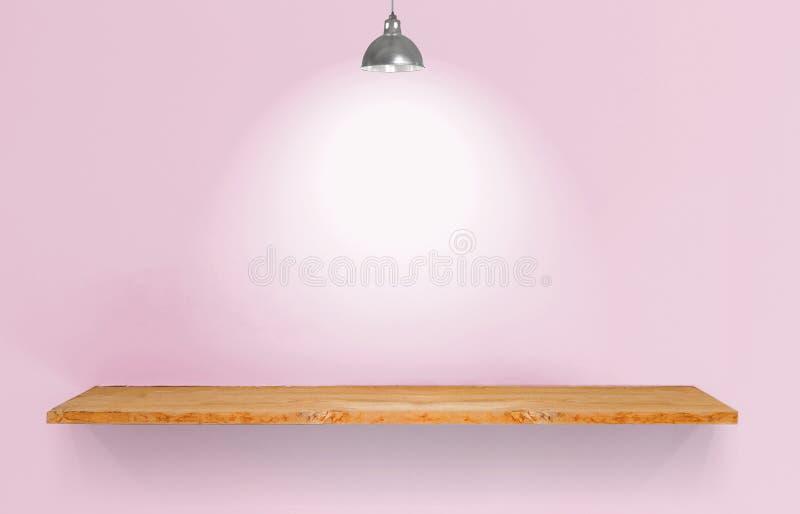Prateleira de madeira com a lâmpada na parede cor-de-rosa do vintage imagem de stock royalty free