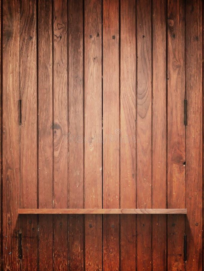 Prateleira de madeira na parede com luz fotografia de stock royalty free