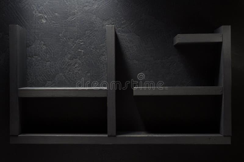 Prateleira de madeira na parede preta fotografia de stock royalty free